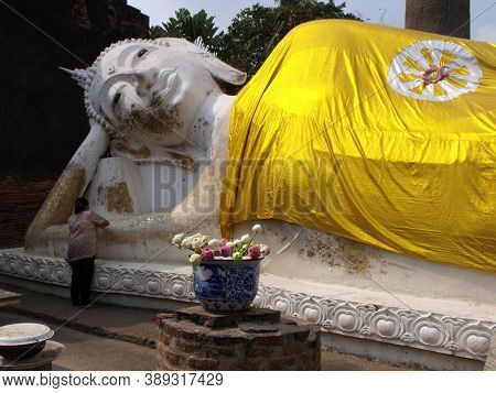 Ayutthaya, Thailand, January 24, 2013: A Woman Places Gold Leaf On The Reclining Buddha In Ayutthaya