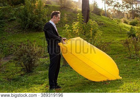 A Young Man Inflates A Yellow Lamzac With Air. A Man Inflates An Air Sofa In Park.