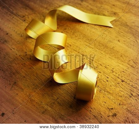 Gold ribbon nicely uncurled, on old wooden desk.