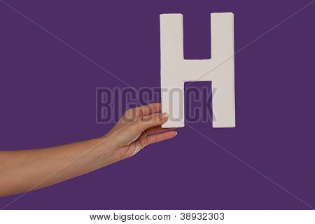 Female hand holding up the uppercase capital letter H isolated against a purple background conceptual of the alphabet, writing, literature and typeface