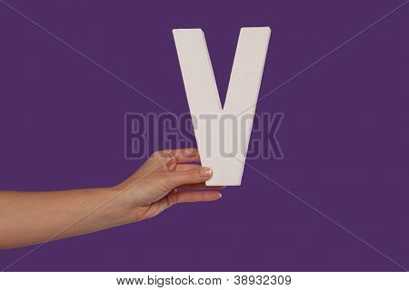 Female hand holding up the uppercase capital letter V isolated against a purple background conceptual of the alphabet, writing, literature and typeface