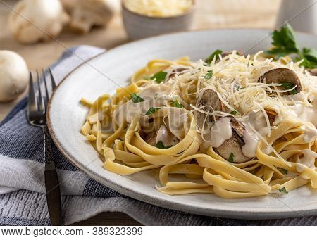 Creamy Fettuccine Alfredo With Mushrooms And Parmesan Cheese On A Plate