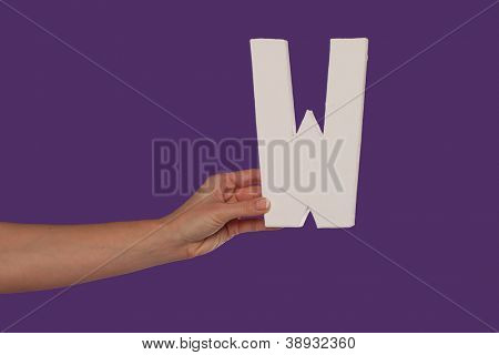 Female hand holding up the uppercase capital letter W isolated against a purple background conceptual of the alphabet, writing, literature and typeface