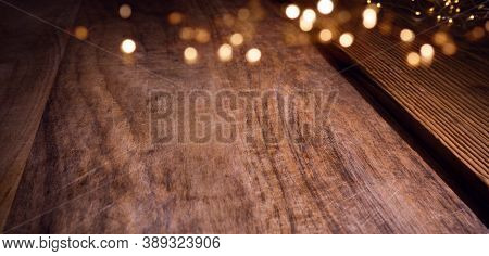 Golden Christmas Bokeh Lights On Aged Wooden Table. Background With Blurred Lights For Your Christma