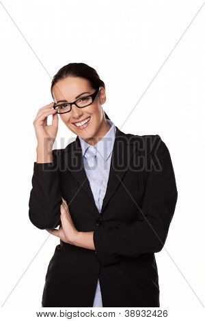 Smiling successful confident businesswoman, manageress or entrepeneur standing with her hand to her glasses isolated on white