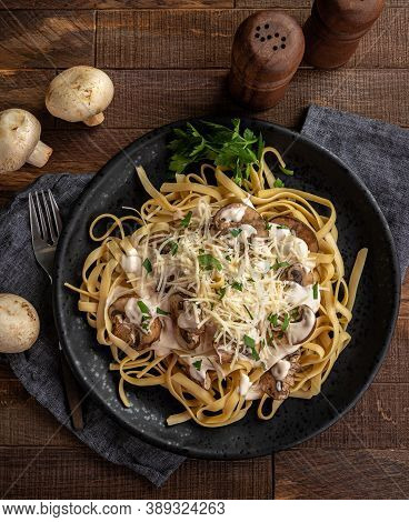 Creamy Fettuccine Alfredo With Mushrooms And Shredded Parmesan Cheese On A Black Plate.  Overhead Vi