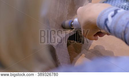 Professional Woman Carpenter Using Hand Rotary Tool, Polishing Wood Product At Workshop - Close Up.