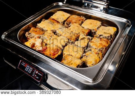 Silver Color Steam Table Of Delicious Portioned Hot Lasagne On Black Background
