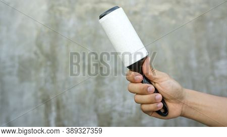 Man Holding A Hair Removal Roller On A Gray Background.