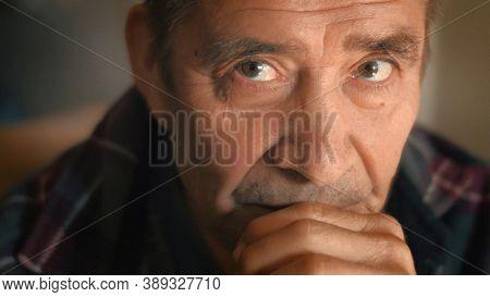 Serious elderly man thinking, looking at camera, closeup. Shallow DOF
