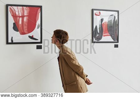 Wide Angle Portrait Of Tattooed Young Woman Looking At Paintings And Listening To Audio Guide At Mod