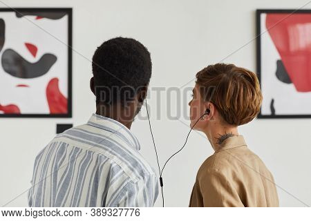 Back View Portrait Of Two Young People Looking At Paintings And Sharing Audio Guide While Exploring