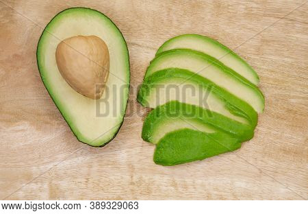 Avocado Cut In The Middle On A Wood Cutting Board. Raw Avocado On Wooden Background. Ripe Avocado Cu