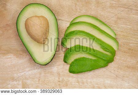 Avocado Cut In The Middle On A Wood Cutting Board. Raw Avocado On Wooden Background. Ripe Avocado Cu