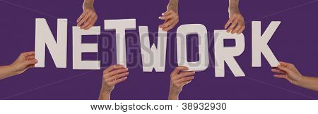 White alphabet lettering spelling NETWORK held up over a purple studio background by outstreched female hands