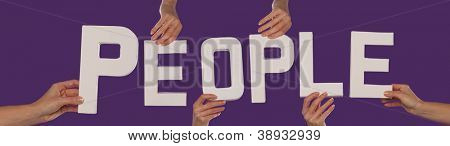White alphabet lettering spelling PEOPLE held up over a purple studio background by outstreched female hands