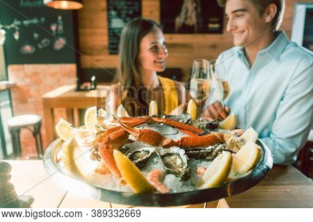 Close-up of fresh oysters and crabs served on ice with slices of lemon at the table of a romantic young couple eating at restaurant