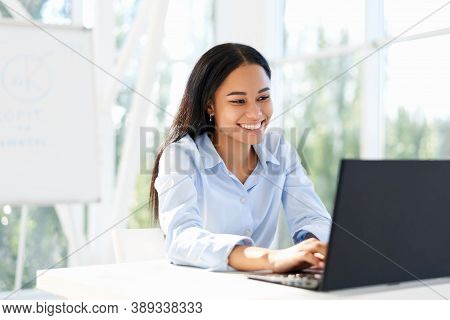 Smiling African American Businesswoman Working On Laptop Sitting At Her Desk In Modern Office. Busin