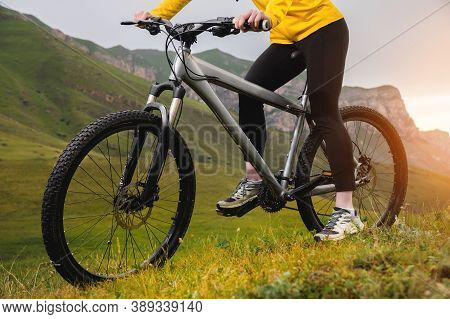 A Young Woman In A Helmet And With A Backpack Stands With A Bicycle And Looks At The Mountains In Cl