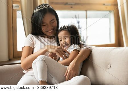 Overjoyed Asian Mother And Little Daughter Having Fun, Tickling