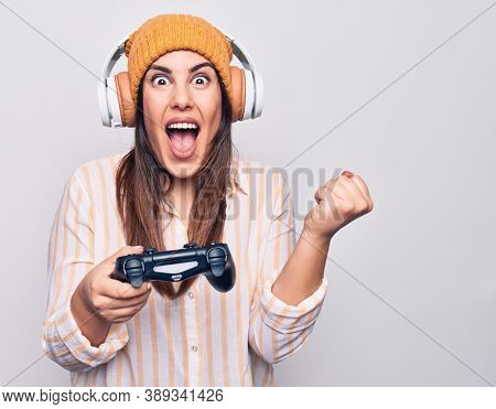 Young beautiful brunette gamer woman playing video game using joystick and headphones screaming proud, celebrating victory and success very excited with raised arm