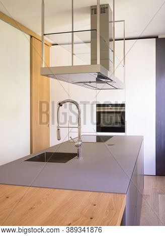 Modern kitchen with suspended hood, large sink, oven and wooden worktop. Detail of modern sink. Nobody inside