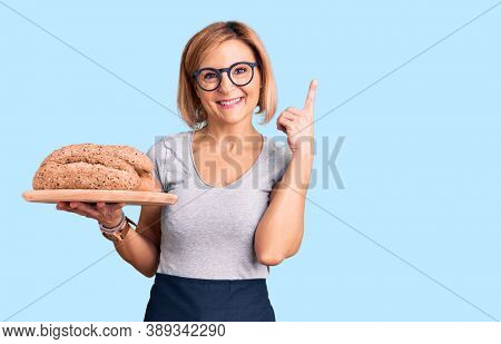 Young blonde woman holding wholemeal bread surprised with an idea or question pointing finger with happy face, number one
