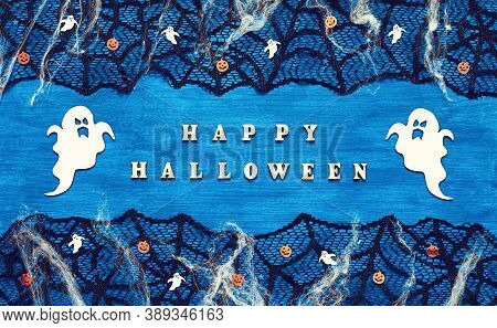 Halloween background. Happy Halloween letters and Halloween decorations on the dark blue wooden background, Happy Halloween holiday concept, Halloween card