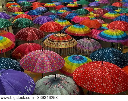 Plenty of hanging colorful umbrellas. An art installation made with many beautiful umbrellas.