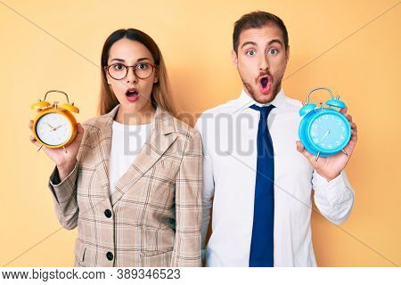 Beautiful couple wearing business jacket and holding alarm clock afraid and shocked with surprise and amazed expression, fear and excited face.