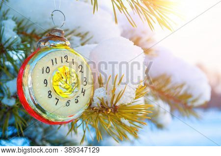 New Year card. New Year background -New Year glass Christmas toy in the form of clock showing the New Year Eve, on snowy fir tree branch. New Year card with vintage Christmas toy, New Year background