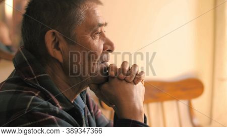 Happy calm relaxed senior man sitting at dinner table at home, looking ahead, thinking. Portrait, closeup