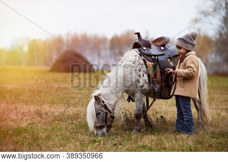 Horizontal side view shot of little girl wearing warm coat spending time with her pony on autumn hayfield