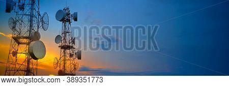Telecommunication Towers With Wireless Antennas On Sunset Sky