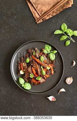 Thai Beef Stir-fry With Pepper And Basil On Plate On A Dark Stone Background. Top View, Flat Lay
