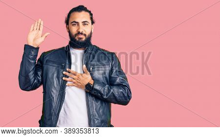 Young arab man wearing casual leather jacket swearing with hand on chest and open palm, making a loyalty promise oath