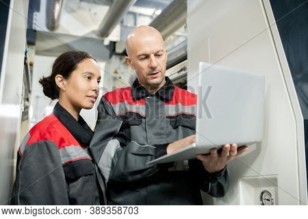 Confident bald mature foreman in workwear holding laptop while making presentation of new materials to young female subordinate