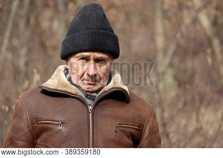 Portrait Of Harsh Elderly Man Standing In Autumn Park. Concept Of Old Age, Life In Village