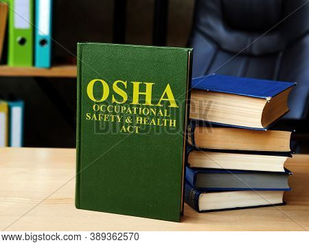 Occupational Safety And Health Act Osha Book And Stack Of Documents.