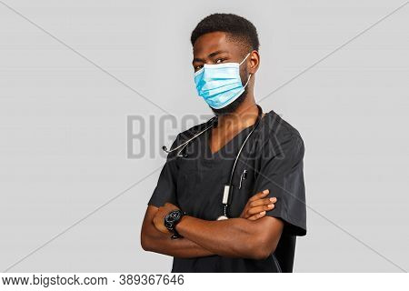 Confident Male Doctor. Cheerful African Doctor In Medical Mask Standing Against Gray Background