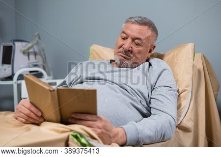 A Gray-haired Old Man Reading A Book In His Bed In A Hospital Ward.