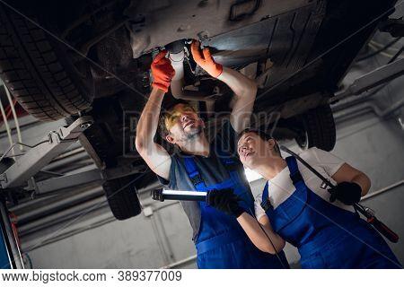 A Female Mechanic Is Holding A Flashlight. Mechanic Repairing A Lifted Car