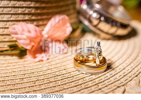 Composition Of Two Wedding Rings Or Bands And Engagement Ring With Diamond On Blurred Background Of