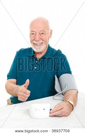 Senior man succeeds in lowering his blood pressure and gives a thumbs up sign.  White background.