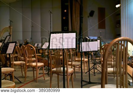 Perm, Russia - October 06, 2020: Empty Concert Hall Stage With Chairs And Musical Scores Before A Sy