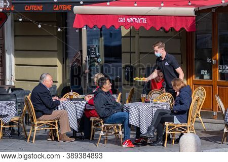 Vilnius, Lithuania - October 12 2020: Waiter With Mask Serving Food At The Table At An Outdoor Bar,