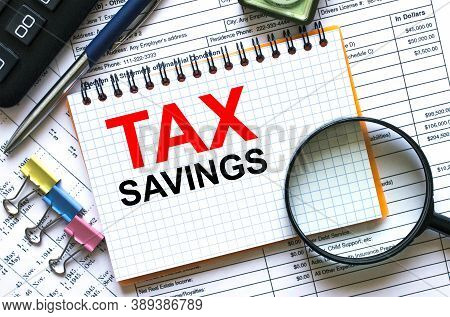 Text Tax Savings On Notepad With Calculator, Clips, Pen On Financial Report