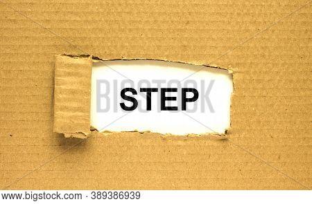 The Word Step Appearing Behind Torn Brown Paper