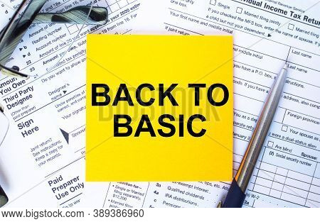 Text Back To Basic On Note Paper With The U.s Irs 1040 Form,pen And Glasses
