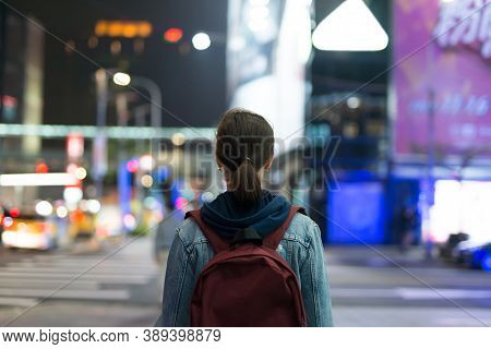 Woman Walks Through The Night City. The View From The Back.